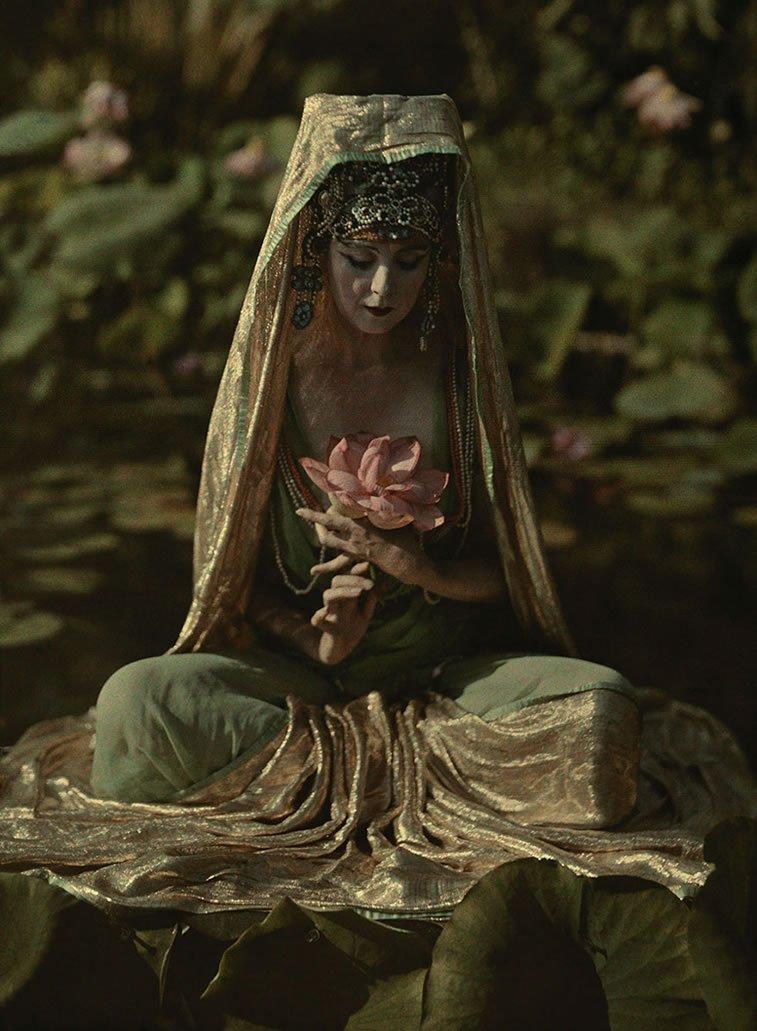 žena prerušena u kinesku boginju pozira u kalifornijskoj bašti 1915.