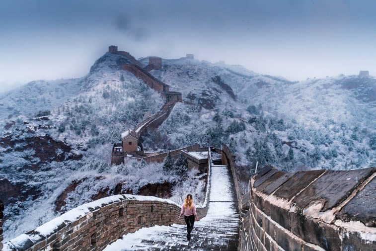 woman walkinhg down the great wall of china in snow