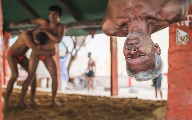 wrestling veteran Siya hanging upside down at Kushti wrestling school in Varanasi, India