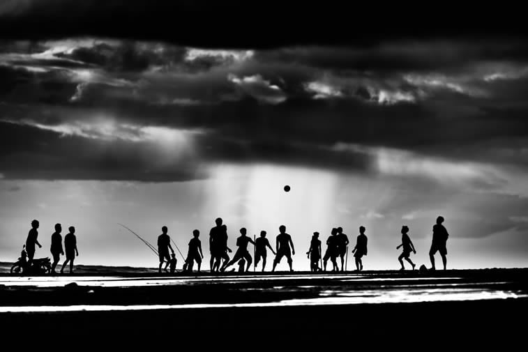 children playing on the Pekutatan beach in Bali silhouettes stormy clouds