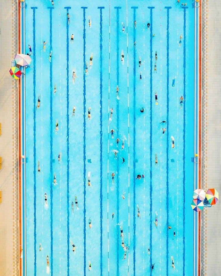 swimming pool swimmers birds eye umbrellas
