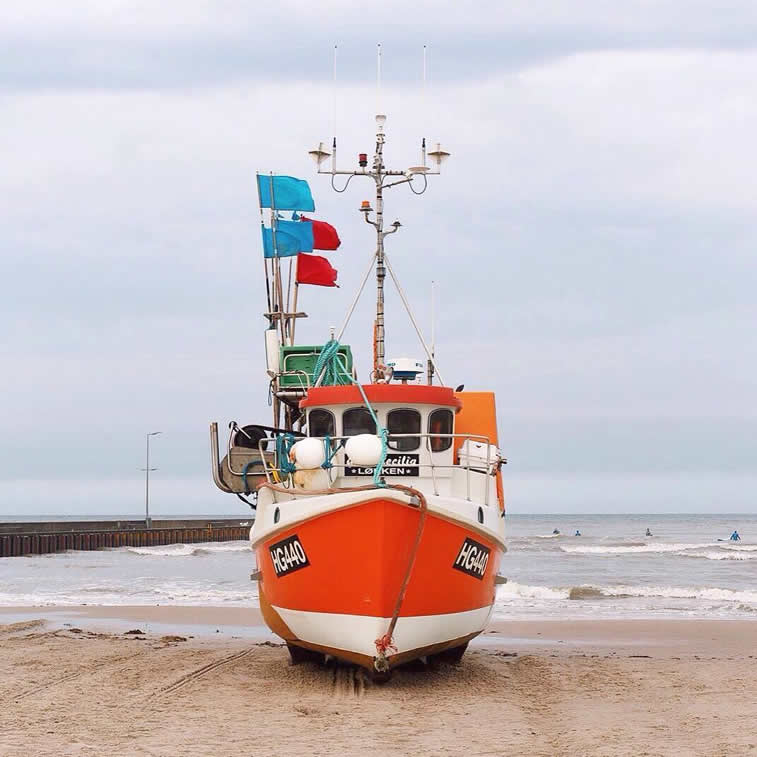 colorful ship on shore accidentally wes anderson