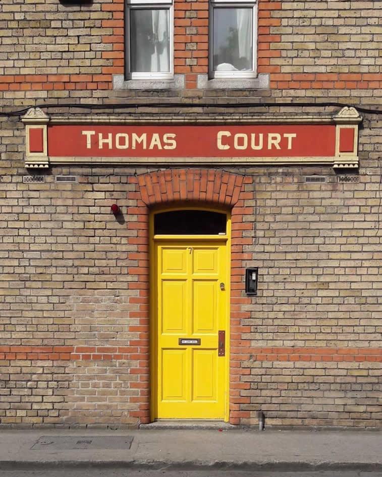 thomas court yellow doors brick building