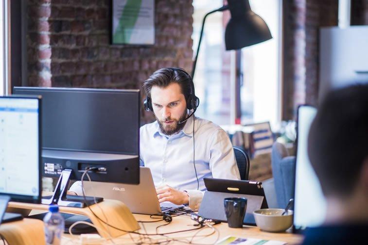 man sitting at workplace multitasking