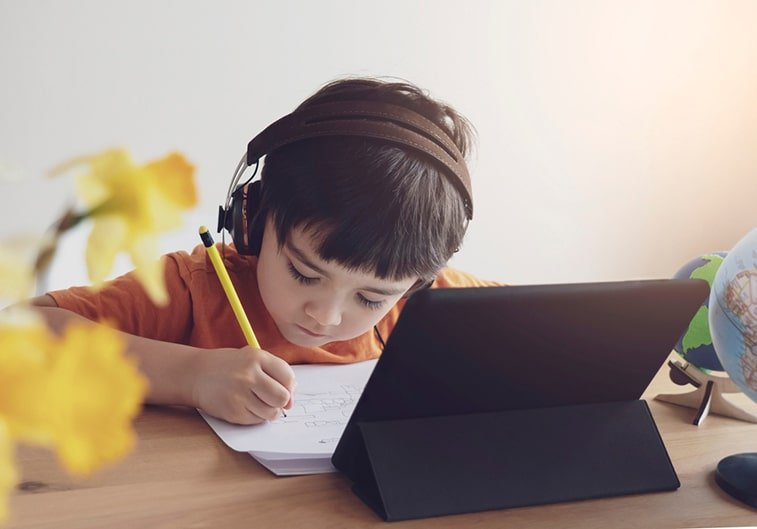 boy writing in front of a laptop